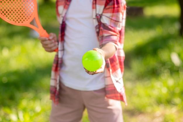 Zomer, tennis. kinderhand die zich uitstrekt naar voren heldere tennisbal buitenshuis op zonnige dag, geen gezicht