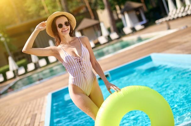 Zomer tijd. een schattige lachende jonge vrouw met een buis bij het zwembad