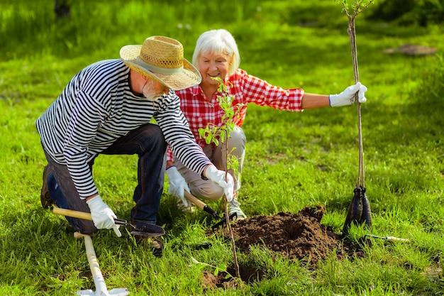 Zomer tijd. knappe mooie man en vrouw die in een huisje wonen in de zomer bomen planten