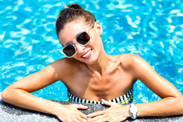 Zomer trendy close-up mode portret van sexy gelooide vrouw ontspannen en zwemmen bij zwembad. lichte bikini en zonnebril dragen, glimlachend en kijkend