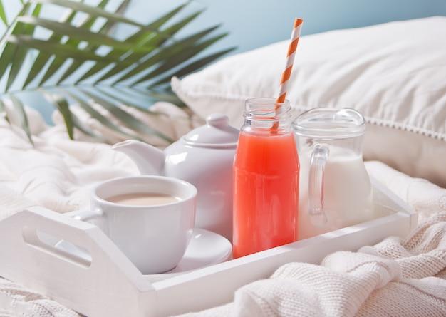 Zomer tropisch ontbijt met kopje thee, theepot en verfrissend exotisch sap in een fles met stro op een wit dienblad onder het palmblad