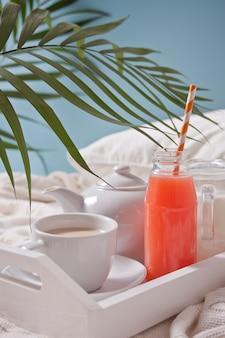 Zomer tropisch ontbijt met kopje thee, theepot en verfrissend exotisch sap