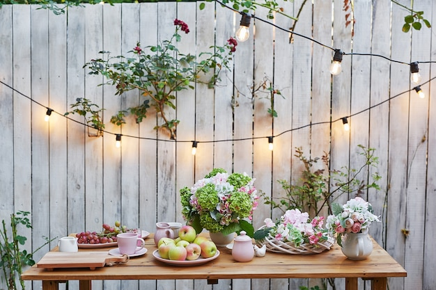 Zomer tuin achtergrond. boeket bloemen hortensia's en kopje thee op tafel. goede gezellige morgen. picknick in de natuur. moederdag wenskaart. viering