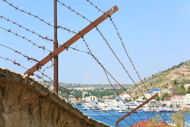 Zomer uitzicht op de kust met schepen op de pier en barblock op de voorgrond (balaclava town, crimea, oekraïne)