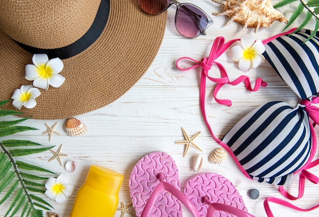 Zomer vakantie concept. strohoed en strandaccessoires met schelpen en zeester op witte houten achtergrond