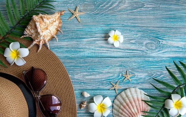 Zomer vakantie concept. strohoed en strandaccessoires met schelpen en zeesterren op blauwe houten ondergrond