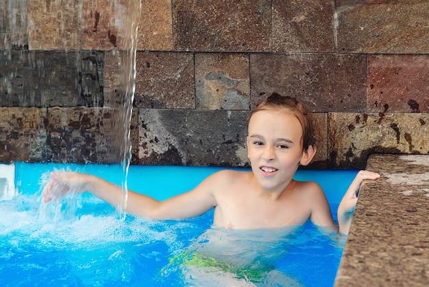 Zomer vakantie concept. waterspelletjes en waterpret voor kinderen. leuke jongen die plezier heeft in het zwembad.