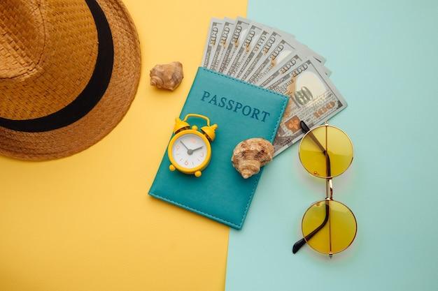 Zomer vakantie concept. zonnebril, hoed en paspoort met geldbankbiljetten op blauwe gele achtergrond