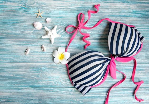 Zomer vakantie concept. zwemtop voor dames, frangipanibloem en schelpen op blauwe houten ondergrond