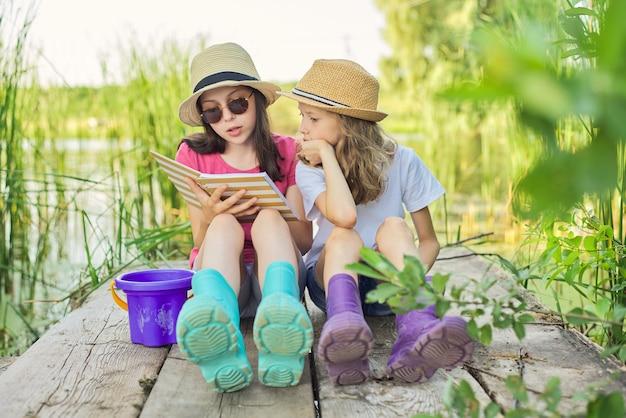 Zomer, vakantie, natuur, levensstijl, vrije tijd voor kinderen. kinderen, twee meisjes zittend op een houten pier in het rietmeer, pratend en lezend notitieboekje met interesse