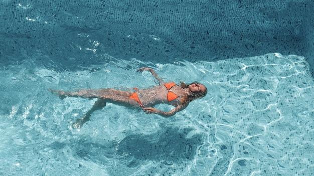 Zomer, vakantie, slank jong meisje liggend op haar rug in een zwembad in een oranje bikini, bovenaanzicht.