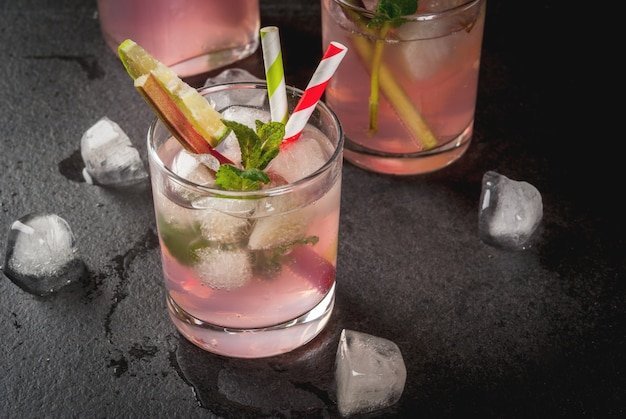 Zomer verfrissend drankje cocktail zelfgemaakte biologische mojito of limonade met rabarber munt en limoen op een zwarte betonnen stenen tafel in glazen en een fles