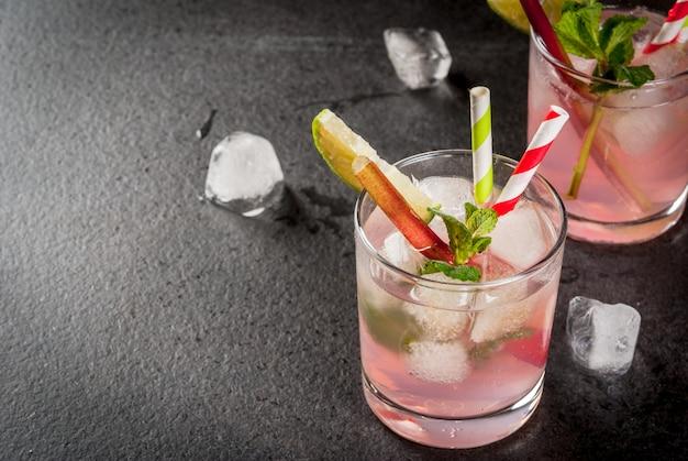 Zomer verfrissend drankje, cocktail. zelfgemaakte organische mojito of limonade met rabarber, munt en limoen. op een zwarte betonnen stenen tafel, in glazen en een fles.