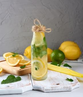 Zomer verfrissend drankje limonade met citroenen, muntblaadjes, limoen in een glazen fles