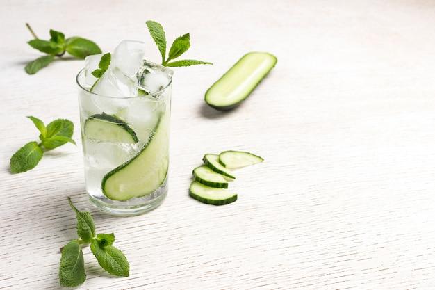 Zomer verfrissend drankje met ijs en plakjes komkommer. munt en gehakte komkommer op witte achtergrond. detailopname. bovenaanzicht