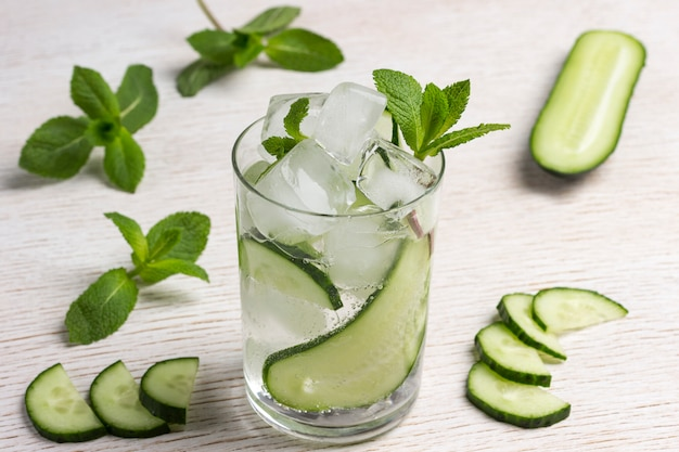 Zomer verfrissend drankje met ijs en plakjes komkommer. munt en gehakte komkommer op witte achtergrond