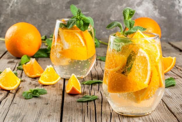 Zomer verfrissend oranje drankje. detox, dieet, toegediend. variaties op limonade. mineraalwater met stukjes verse sinaasappel en munt. op een rustieke houten tafel met grijze muur. verticaal, kopieer ruimte