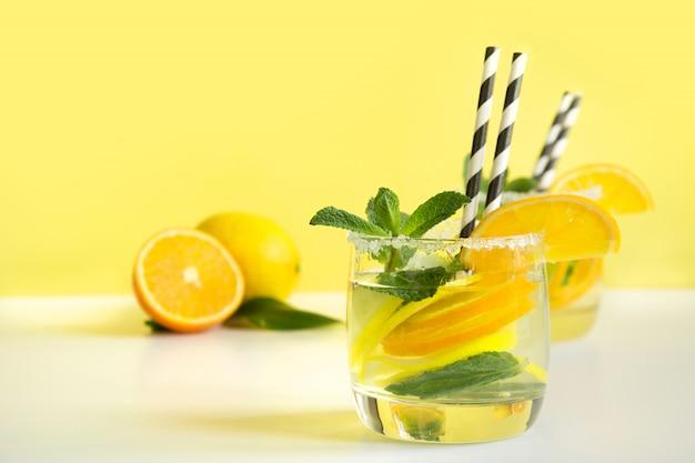 Zomer verfrissende cocktail met citroen, sinaasappel, munt en ijs in glas op geel. tropisch concept.