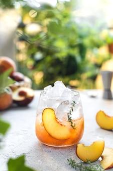 Zomer verfrissende ijs cocktail met plakjes perzik en tijm