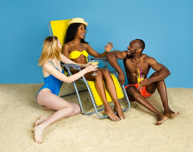 Zomer verhaal. gelukkige jonge vrienden die en pret op blauwe studioachtergrond rusten. concept van menselijke emoties, gezichtsuitdrukking, zomervakantie of weekend. chill, zomer, zee, oceaan.