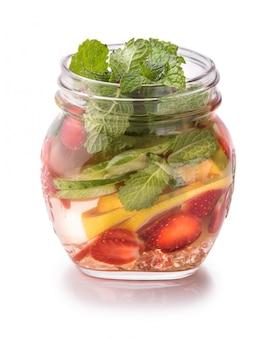 Zomer vers fruit op smaak gebrachte watermix van limoen, komkommer, aardbei en munt die over witte achtergrond wordt geïsoleerd