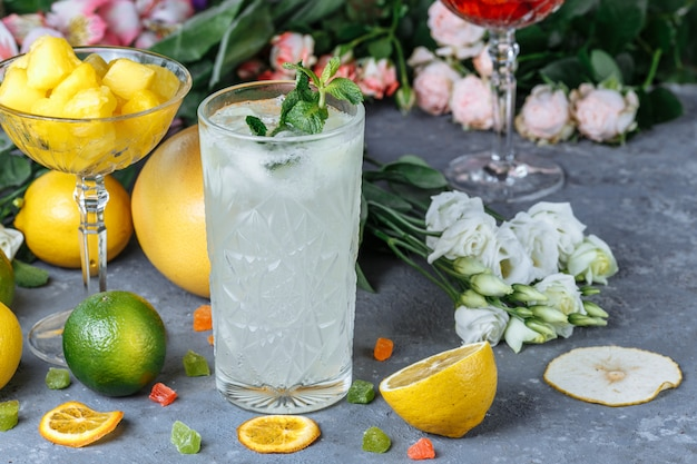 Zomer verse koude dranken. ijs limonade in de kruik en citroenen en oranje met munt op tafel buiten.