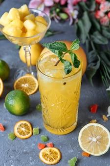 Zomer verse koude dranken. ijs limonade in de kruik en citroenen en sinaasappel met munt op tafel buiten. oranje limonade in een glas.