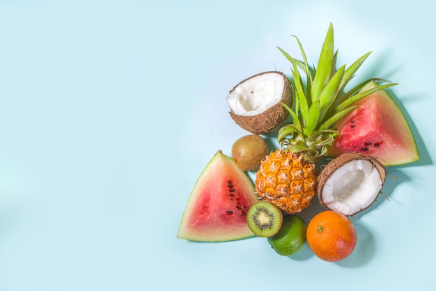 Zomer vitamine voedsel concept, verschillende fruit en bessen achtergrond - watermeloen ananas appels kiwi kokosnoot oranje limoen creatieve plat leggen
