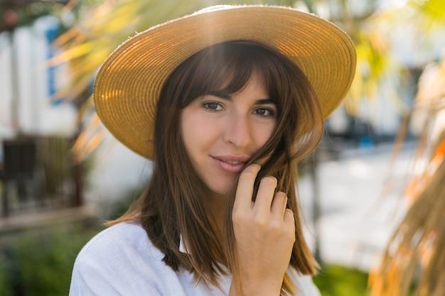 Zomer vportrait van vrij brunette vrouw in strooien hoed poseren buiten.