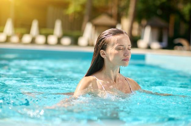 Zomer vreugde. een mooie slanke vrouw in een zwembad