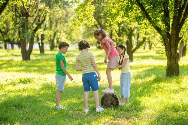 Zomer vrije tijd. langharig meisje dat op een zonnige dag op een boomstronk staat en vrienden samen op een groen gazon