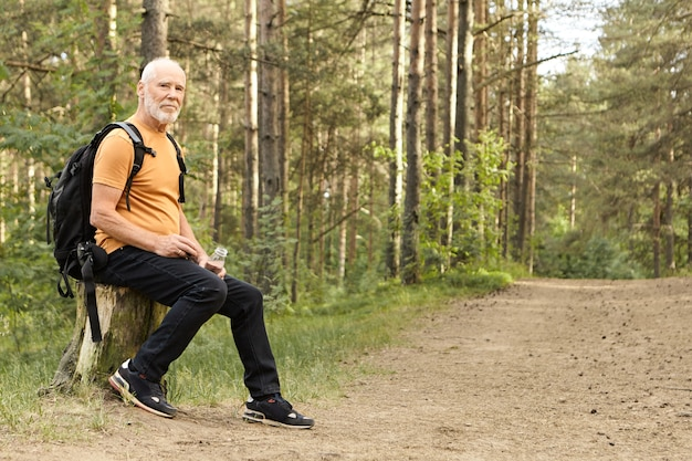 Zomer, wandelen, actieve levensstijl en leeftijdsconcept. energieke blanke man op pensioen zomerdag buiten in de wilde natuur doorbrengen, te voet reizen, rust op boomstronk met fles water