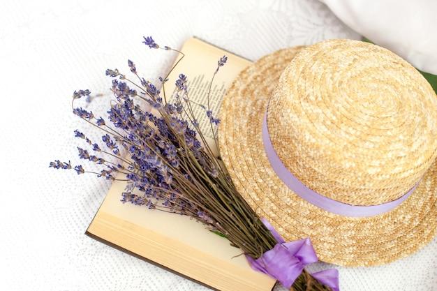 Zomer weekend concept. ik lees de roman en rust uit. geopend boek, lavendel en stro hoed, bovenaanzicht. provence en rustieke stijl. biologische lavendel, aromatherapie. shabby chic stijl. een boek lezen. wijnoogst