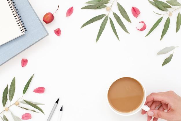 Zomer werkplek met hand en kopje koffie op witte tafel, kopie ruimte achtergrond.