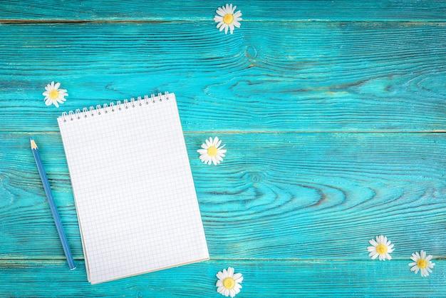 Zomer werktafel met notebook en chamomiles bloemen op blauwe houten tafel, plat leggen