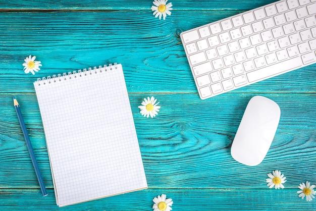 Zomer werktafel met toetsenbord, computermuis en chamomiles bloemen op blauwe houten tafel, plat leggen