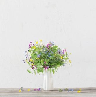 Zomer wilde bloemen in vaas op wit oppervlak