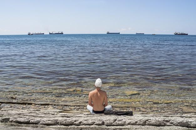 Zomer zee landschap. een man zit op een wild stenen strand en kijkt in de verte. aan de horizon is een strakblauwe lucht en vrachtschepen.