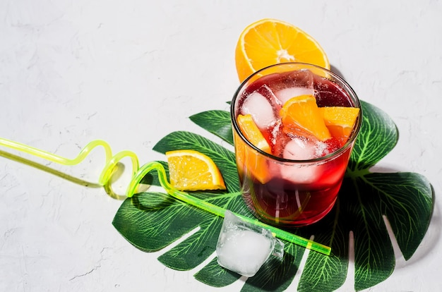Zomer zelfgemaakte koude rode sangria cocktail met sinaasappel en ijs in glas op grijze betonnen steen b