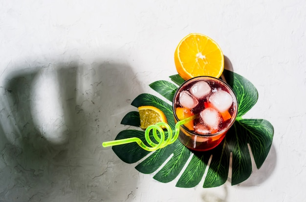 Zomer zelfgemaakte koude rode sangria cocktail met sinaasappel en ijs in glas op grijze betonnen steen