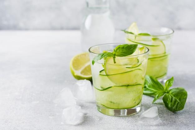 Zomer zelfgemaakte limonade gemaakt van limoen, citroen, komkommer en basilicum met ijs in glas op een oud beton.