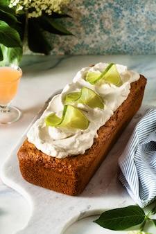 Zomer zoete broodcake op een tafel met bloemen en een drankje in glazen. met kokosroom en limoen. dessert voor brunch of ochtendontbijt