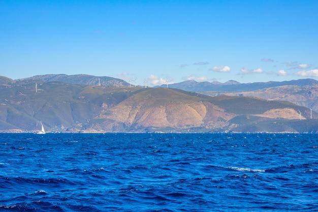 Zomer zonnige dag en de heuvelachtige kust met windmolenparken. eenzaam zeiljacht