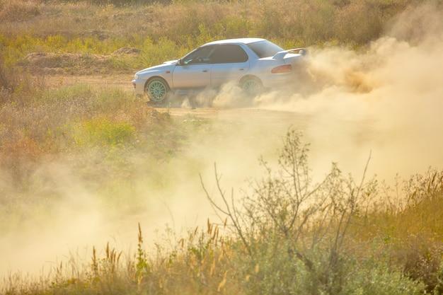 Zomer zonnige dag. onverharde weg voor de rally. een auto rijdt door een bocht en maakt veel stof 01