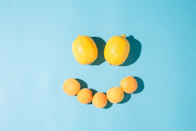 Zomer zonnige leuke compositie van gele citroenen gerangschikt in de vorm van een lachend gezicht op blauwe achtergrond. minimale natuurlijke platligging