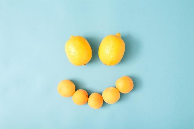 Zomer zonnige leuke compositie van gele citroenen gerangschikt in de vorm van een lachend gezicht op blauwe achtergrond