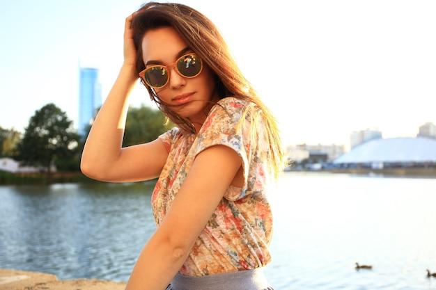 Zomer zonnige levensstijl mode portret van jonge stijlvolle hipster vrouw. vrouw met witte tanden die in de zomer zijwaarts denkt en kijkt in een park