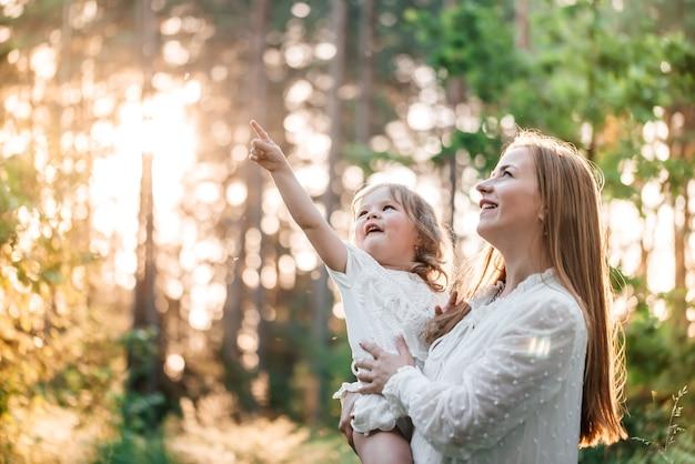 Zomer zonsondergang in het park of bos. babydochter op een ritje op de rug met haar moeder.