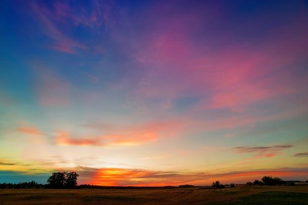Zomer zonsondergang met roze oranje wolken boven het veld