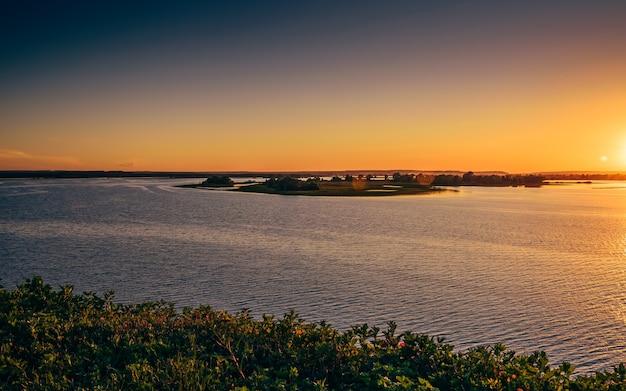 Zomer zonsondergang over de rivier de wolga. klein eiland in het midden.